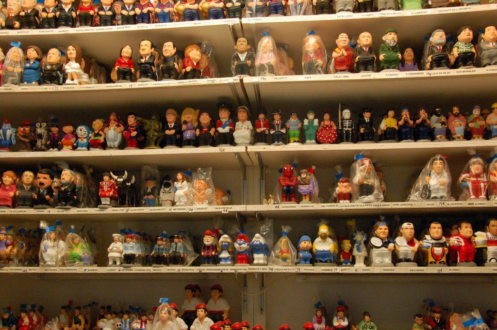Katalońskie Boże Narodzenie. Obrazek z postaciami w sklepie. Podpis: Półki uginają się od caganers. A jaką Ty wybierzesz figurkę?