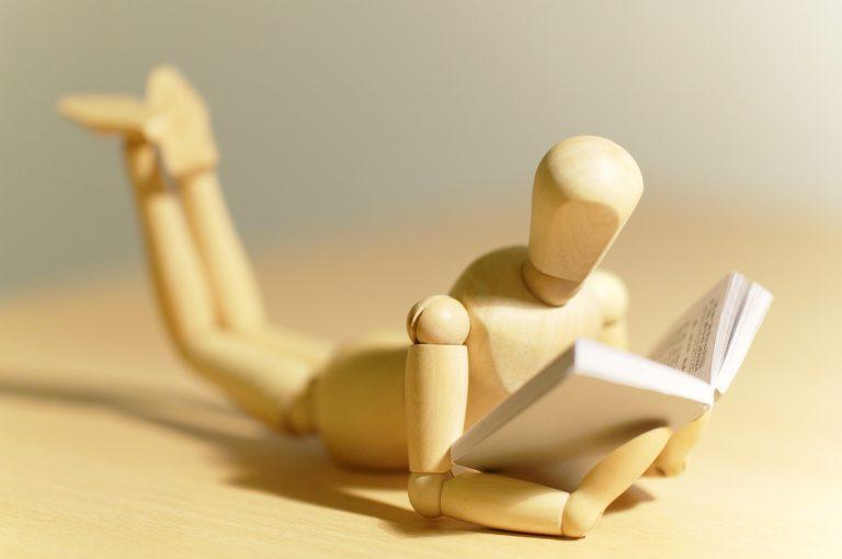 Drewniany ludzik czyta książkę. Tytuł artykułu: Hiszpański na poziomie A1-–A2.