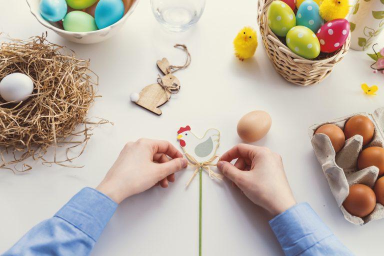 Na stole leżą pisanki w wiklinowych koszyczkach, drewniany królik, włóczkowy kurczak. Czyjeś ręce kończą dekorować drewnianego kogucika. Tytuł: Wielkanoc w Serbii i Słowenii